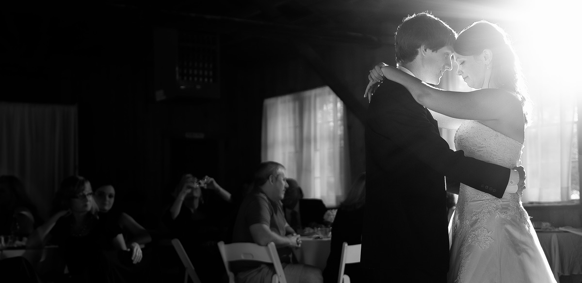 Black and White image of a bride and groom during their first dance with dynamic lighting