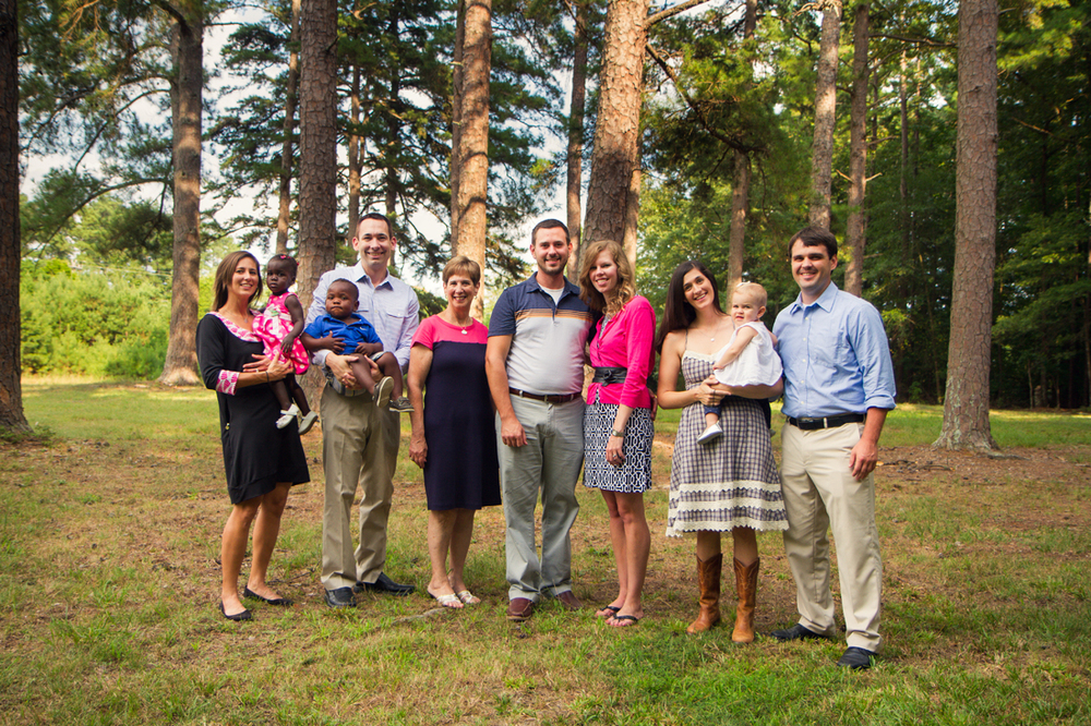 large family portrait in a field in front of pine trees